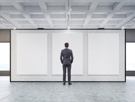 toning: Rear view of a man looking at three large vertical posters situated on a gray wall in a gallery. Concept of modern art and marketing. 3d rendering. Mock up Stock Photo