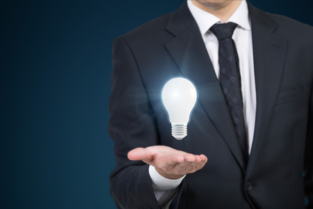 idea: Close up of a businessman in dark suit who has a light bulb floating above his hand. Concept of a brilliant idea. Mock up Stock Photo