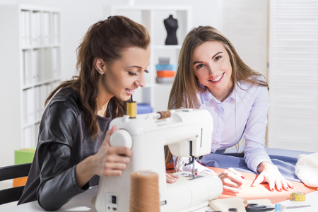 brown haired: Smiling brown haired woman is sewing at a machine. Her colleague is smiling and holding a chalk Stock Photo