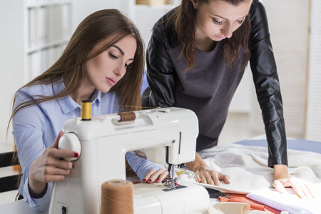Woman in blue shirt is sewing. Her colleague is standing by her side and looking at the pattern on the table Stock Photo