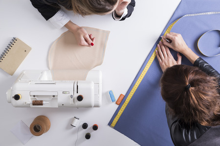 made: Top view of a woman looking at her colleague measuring a blue piece of fabric Stock Photo