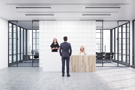 lady clock: People are standing in an office lobby. Large wall is decorated with white tiles. There is a wooden part of it and two conference rooms by both sides. 3d rendering. Mock up Stock Photo