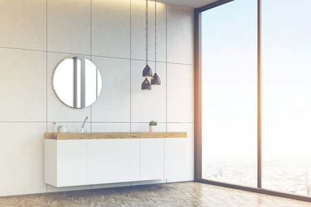 Corner of a bathroom interior with a tiled wall, a round mirror and a long sink counter. 3d rendering. Toned image