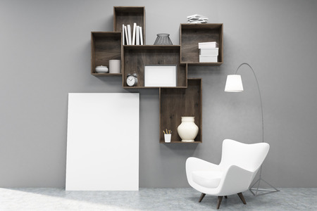 Shelfs with books, vases and boxes attached to a gray wall. There is a large vertical poster under them and an armchair. 3d rendering. Mock up Zdjęcie Seryjne