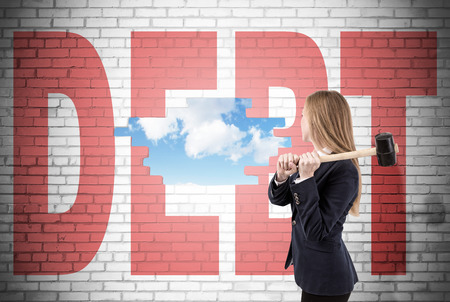 Woman has crashed a white brick wall with sledgehammer and word debt written on it. Sky is seen through the hole. Concept of stabilizing your material situation Stock Photo