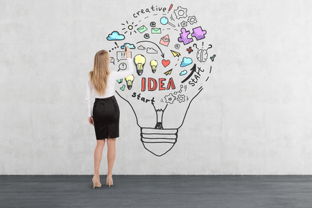 Rear view of blond woman drawing business idea sketch inside a giant light bulb on concrete wall. Concept of creative thinking
