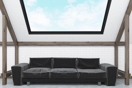 mansard: Close up a large comfortable sofa standing in the attic under the window. Cloudy sky is seen in the background. 3d rendering Stock Photo