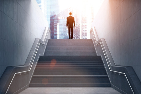 Rear view of a businessman climbing stairs to get to a large city center. Concept of success and appreciation. Toned image Banque d'images