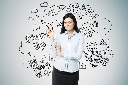 black haired: Smiling black haired woman with pen is standing near project launch sketch drawn on gray wall behind her. Concept of new business model Stock Photo