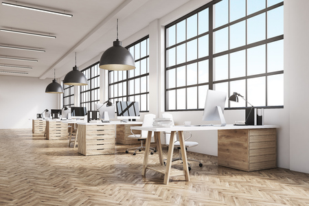 Long office room with wooden floor, long tables with desktops and big ceiling lamps. 3d rendering.