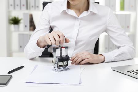 Zamknij się kobieta w białej bluzce, która siedzi w biurze i tłoczenia dokumentu. Pojęcie pracy notariusza