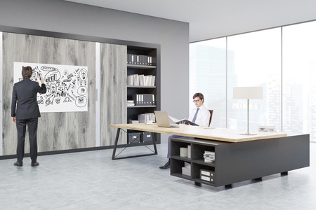 ceo office: Man sitting in a CEO office at a massive wooden table. The second man is drawing on a horizontal poster on the wall. There are wooden doors. 3d rendering. Stock Photo
