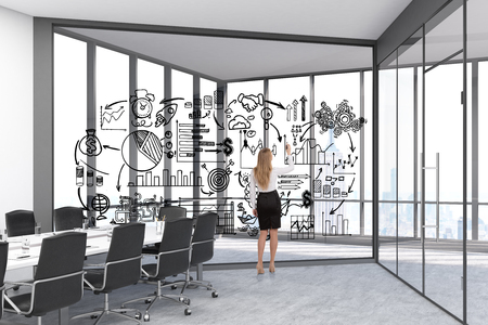 glassboard: Rear view of a businesswoman drawing a sketch on a glassboard in a room with panoramic windows and a conference table. 3d rendering. Stock Photo