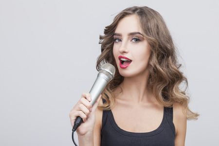 Close up of a singing woman with a large microphone is looking at the camera. She is wearing a black dress. Gray background. Stock Photo