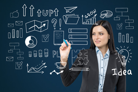 glassboard: Close up of a woman with black hair drawing a business idea sketch on a glassboard in a blue room
