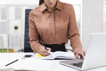 finance manager: Close up of woman in brown blouse typing with one hand and taking notes with the second. Concept of multitasking Stock Photo