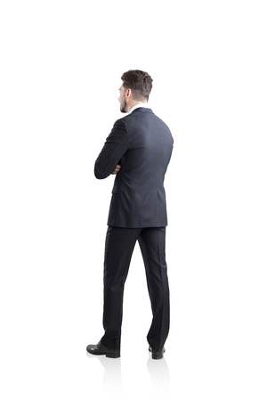 Rear view of a bearded businessman in suit standing with his arms crossed. Concept of a successful businessman. Mock up.isolated over white background. Stock Photo