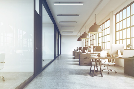 under view: Front view of an office interior with a row of dark wood tables standing under large windows. Massive ceiling lamps. Computers. 3d rendering. Toned image