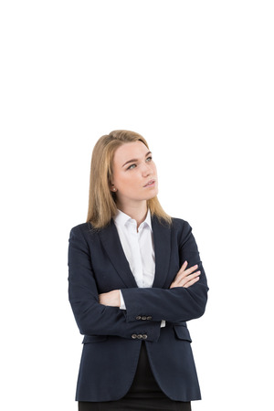 looking upwards: Isolated portrait of a blond businesswoman standing with her arms crossed and looking upwards. Mock up Stock Photo