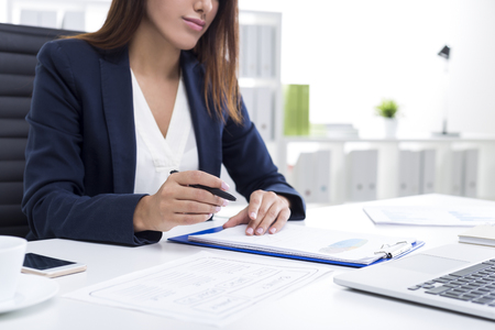 Close up of a businesswoman with tanned skin holding a pen and sitting at her table with a clipboard. Archivio Fotografico