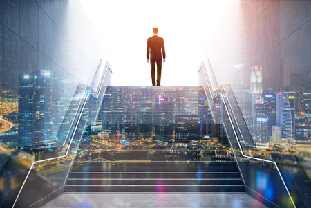 Rear view of a businessman climbing stairs to get to a large city center. Concept of success and appreciation. Toned image. Double exposure