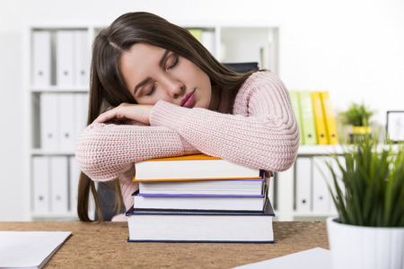 school exam: Portrait of a woman wearing a pink sweater and sleeping on a stack of books in an office. Concept of learning too much Stock Photo