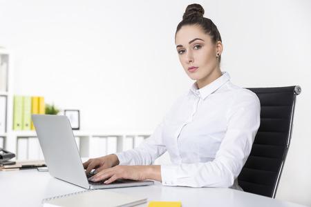 desprecio: Empresaria seria está mirando con desprecio mientras se escribe en su teclado del ordenador portátil