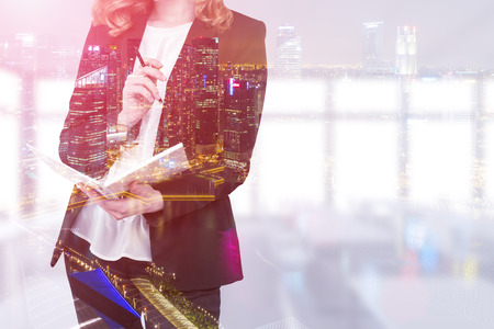 double page: Close up of a redhead businesswoman with a notebook and a pen standing in her office. Large cityscape is seen on the foreground. Toned image. Double exposure. Mock up
