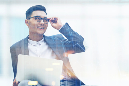 double exposure: Portrait of a successful Asian businessman wearing glasses and a suit. He is sitting in his office with a laptop and smiling. Graphs. 3d rendering. Toned image. Mock up. Double exposure