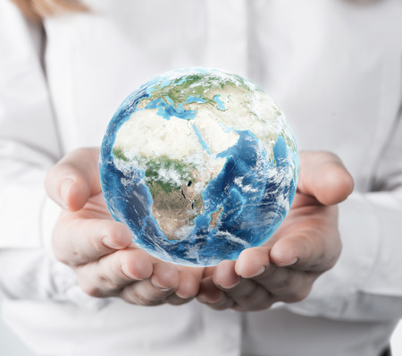 small world: Woman in a white blouse is holding a planet in her hands. Concept of a small world.