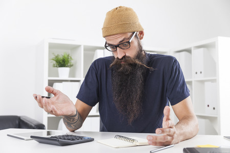 Businessman with long beard wearing a beanie is surprised by the data he has gathered