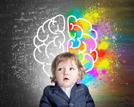 Portrait of an adorable little boy wearing a suit and standing near a chalkboard with a colorful brain sketch. Concept of childs development