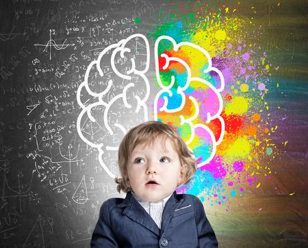 Retrato de um menino adorável, vestindo um terno e parado perto de uma lousa com um desenho colorido do cérebro. Conceito de desenvolvimento infantil