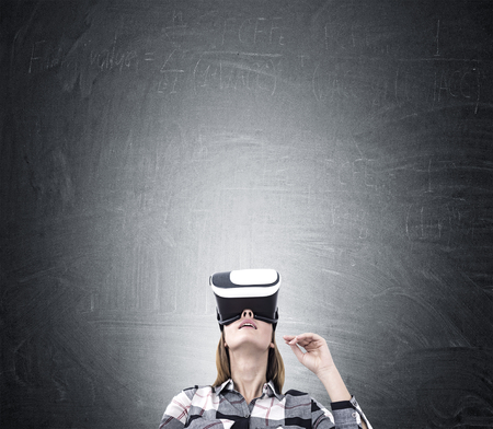 looking upwards: Woman in virtual reality glasses and a flannel shirt is standing near a blackboard and looking upwards. Mock up