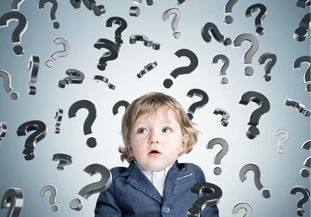 El pequeño bebé con la boca abierta lleva un traje azul y de pie cerca de una pared gris con muchos signos de interrogación.