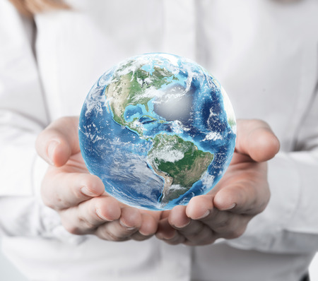 small world: Close up of a woman in a white blouse is holding a planet in her hands. Concept of a small world.