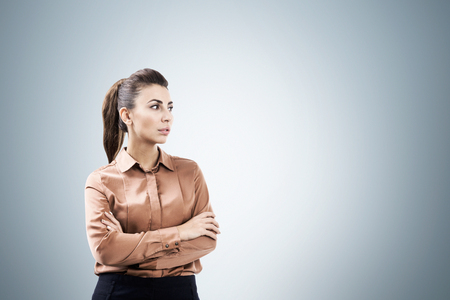 face centered: Portrait of a serious woman standing with her arms crossed and wearing a brown blouse near a gray wall. Mock up Stock Photo