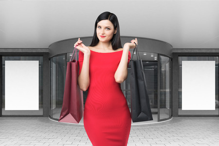 outdoor blank billboard: Close up of a happy woman in a bright red dress is standing with two shopping bags near a mall entrance. Concept of consumerism. 3d rendering. Mock up. Stock Photo