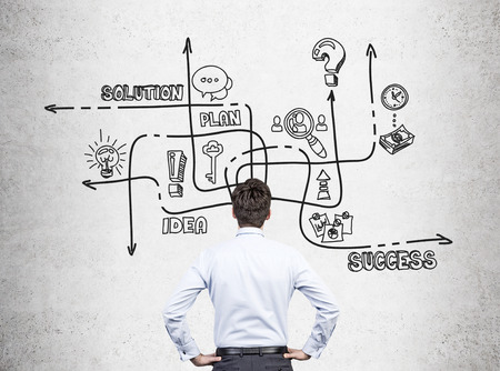 brain storming: Rear view of a businessman wearing a white shirt standing with his hands on the waist and looking at a solution sketch drawn on a concrete wall.