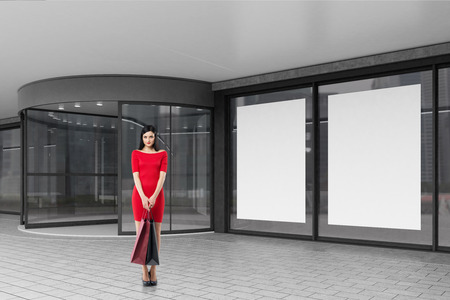 copy center: Woman in a bright red dress is standing with two shopping bags near a mall entrance. Concept of consumerism. 3d rendering. Mock up.
