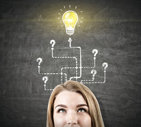 achiever: Close up of a blond businesswomans head  near a blackboard with an arrow labyrinth and a light bulb sketch. Question marks.
