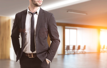 wealthy lifestyle: Close up of a businessmans torso. He is wearing a suit and standing with his hands in pockets. There is a conference room in the background. 3d rendering. Toned image