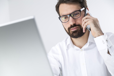 Close up of a young man who is wearing glasses and a beard. He is sitting at his workplace and looking at his laptop screen while talking to a client on the phone.