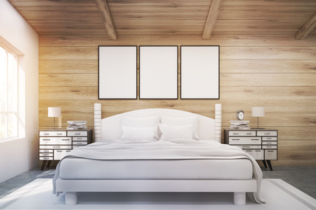 bedside tables: Front view of a double bed in a room with wooden walls and ceiling. There are two bedside tables and two large windows. Three framed posters are above the bed. 3d rendering. Mock up. Toned image