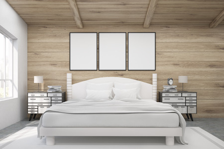 bedside tables: Front view of a double bed in a room with wooden walls and ceiling. There are two bedside tables and two large windows. Three framed posters are above the bed. 3d rendering. Mock up.