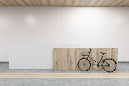 standing reception: Front view of a wooden reception counter with a bicycle standing near it. Concrete and wooden floor, white walls. 3d rendering. Mock up