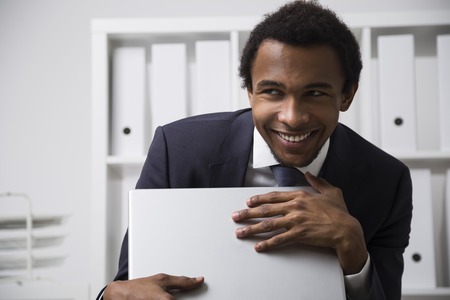Portrait of a very shy African American office clerk working in a white office, smiling and grasping his laptop as a treasure. Concept of shyness and social awkwardness Stock Photo