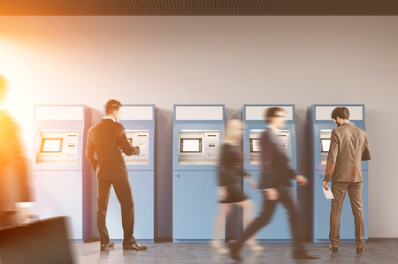Hallway of an office or a bank. People are rushing by. Two businessmen are standing near ATM machines. There is a cityscape on the foreground. Toned image. Banque d'images