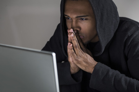 plotting: Close up of an African American hacker in a hoodie plotting his next attack. Concept of internet wars and information security