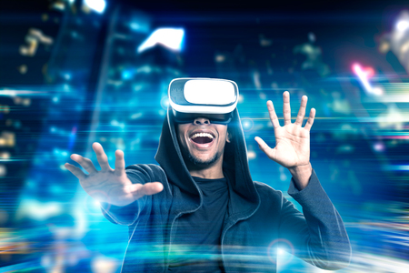 double game: Portrait of an excited African American man in virtual reality glasses playing a game in a night city. Toned image. Double exposure Stock Photo